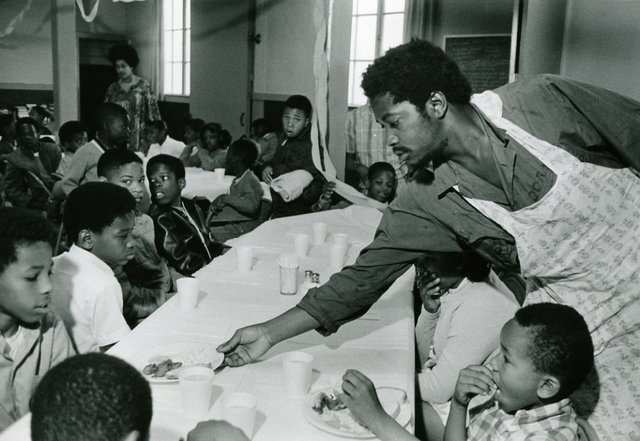 #2 Charles Bursey hands plate of food to a child seated at Free Breakfast Program.  Photo courtesy of Pirkle Jones and Ruth-Marion Baruch.PJ_v1CROPPED.jpg